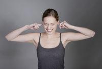 junge Frau hält sich die Ohren zu