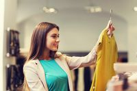happy young woman choosing clothes in mall