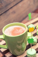 Hot cocoa in green cup and green macaroon cookies scattered on the wooden surface with St. Patrick's Day attributes. Tinted photo. Shallow depth of field. Copy space