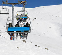 Skiers and snowboarders on chair-lift