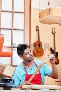 Mann als Lehrling baut eine neue Gitarre