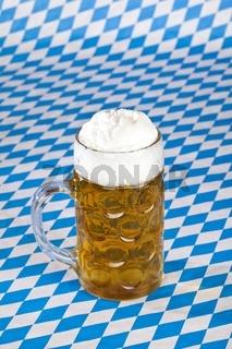 Oktoberfest Maßkrug mit Schaumkrone und bayerischer Flagge