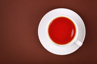Full white cup of red black tea on brown