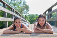 Two friends lying together on wooden bridge