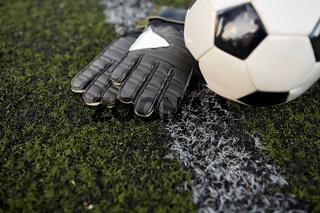 soccer ball and goalkeeper gloves on field