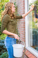 Young european woman washing house window outdoors