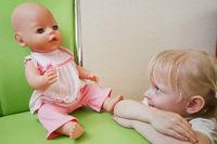 Mädchen mit Puppe auf einem Stuhl