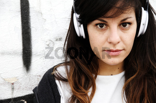 Girl listening to Music while leaning on a Wall