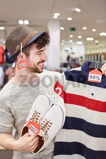 Mann hält Kleidung mit 50% Rabatt Discount