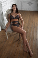 Very sexy brunette lady posing in black lingerie, sitting on chair.