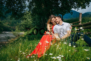 Happy laughing couple is tenderly hugging while sitting on the chamomile meadow under the tree near river and wooden fence. The pretty blonde woman with the bouquet.
