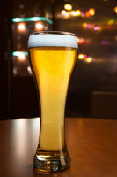 Tall glass of beer in bar