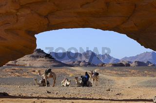 Kamelkarawane lagert vor einem Felsentor, Sahara