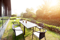 table and chairs near modern building with sunbeam