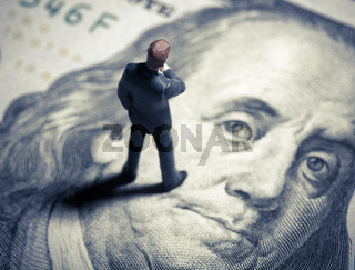 Miniature figurine businessman with 100 dollars. Top view.