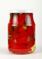 Jar of pickled red hot chili peppers over white