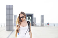Young girl traveler with backpack looking on phone