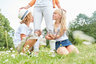 Kinder küssen liebevoll die Beine ihrer Mutter