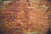 Grunge brick wall with peeling orange paint