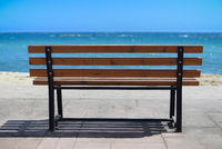 Empty wooden rest bench at sea shore