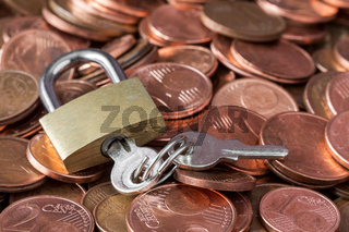 Pile of coins and a padlock with keys