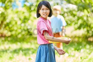 Asiatisches Mädchen spielt Frisbee