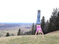 sportliches Mädchen macht Handstand am Berg