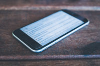 phone isolated on wooden background macro - smartphone closeup