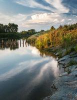 Abendlicht und Wolken spiegeln sich im See im Burgenland