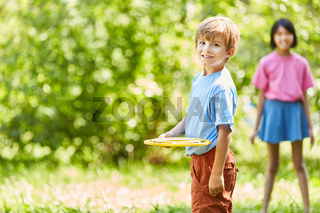 Junge spielt Frisbee mit einem Mädchen