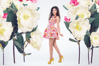 Concept fashion portrait of young beautiful woman with oversized flowers garden