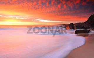 Foamy white seas and vivid sunrise