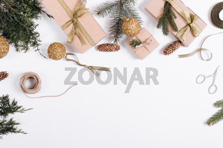 Christmas decorations on a white background: branches of fir, gift boxes, ribbons, toys, rope, scissors