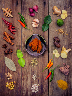 Various of Thai food Cooking ingredients and spice red curry paste ingredient of thai popular food on rustic wooden background. Spices ingredients chilli ,pepper, garlic nutmeg and Kaffir lime leaves.