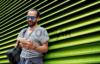 man with earphones and smartphone over wall