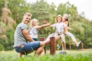 Vater schaukelt mit Kindern auf dem Spielplatz
