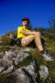 Frau (22) sitzt am Berg und geniesst die Abendsonne