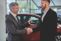 Car seller and buyer shaking hands in auto showroom.
