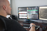 Man Programming Code On Computers Screen At Desk.