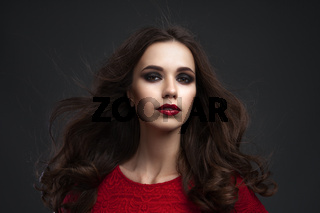 Portrait of the beautiful young woman with long brown hair posing at studio