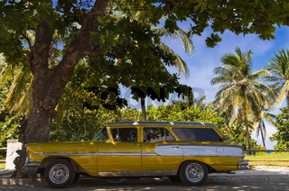 Amerikanischer gold gelber Oldtimer parkt in Varadero  nahe des Strandes in Kuba