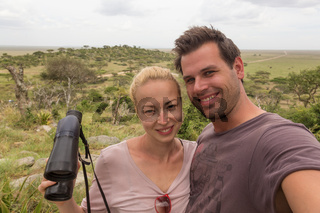 Adult couple taking selfie on african wildlife safari in Serengeti national park, Tanzania, Africa.