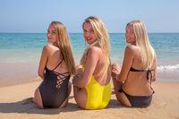 Three girls sitting on beach looking back