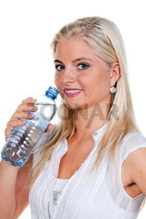 Frau hat Durst und trinkt Mineralswasser aus Petflasche