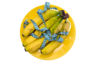 Banana fruits and measuring tape on the plate