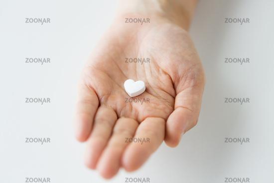 close up of hand holding medicine heart pill