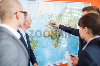 Gruppe Geschäftsleute plant Expansion an Weltkarte