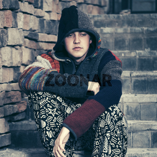 Sad young fashion hippie man sitting on the steps