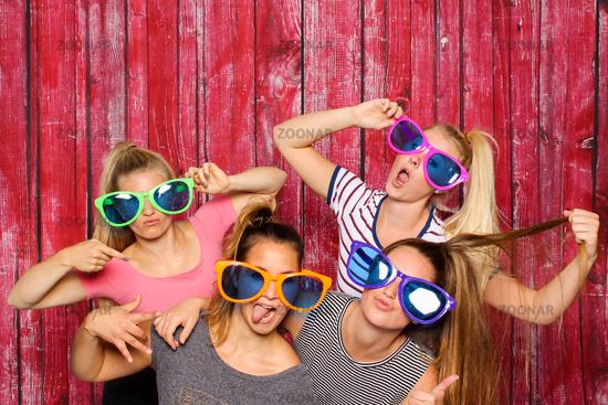 alberne mädchen mit sonnenbrillen vor photobooth