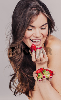 Young girl eating strawberry